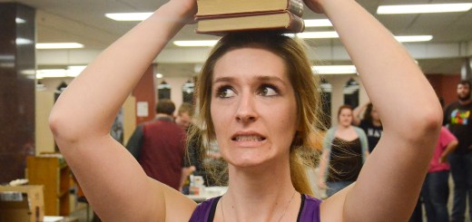 Kelsey Empfield, Senior, balances books on her head Monday during the Book Balance Challenge at the Nerd Triathlon in the Library Commons. — Photos by Ashley Swanson