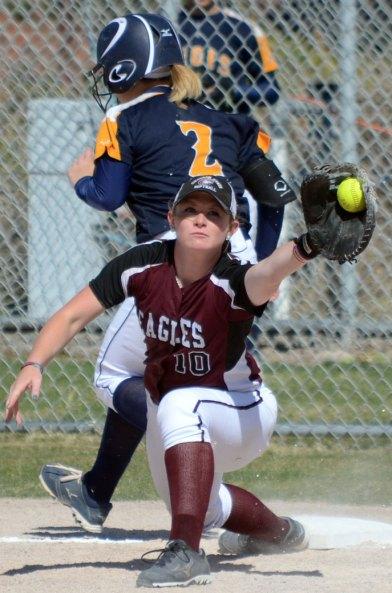 Regis University's Emily John (2), freshman of Beaverton, Oregon, narrowly escapes as first baseman junior Katelyn Kruger (10), of Highlands Ranch, Colorado, snags the ball April 4.  —Photo by Christopher Smith