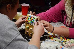 Kelsey Vincent, 19, sophomore of Oshkosh, left, and Austin Hackney, 19, sophomore of Paxton, build and decorate a house last Thursday during Late Night Gingerbread House Making.--Photo by Teri Robinson