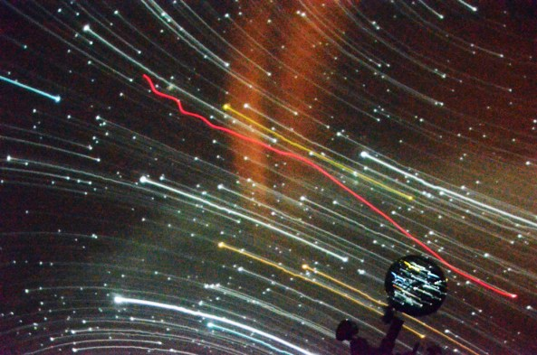 """Caelum Hubl, freshman of Lincoln, uses a laser to point out constellations during his presentation. This image shows """"star trailing,"""" which is catching the movement of the stars, Friday, in the planetarium in the Math and Science building. —Photo by Sara Tweet"""