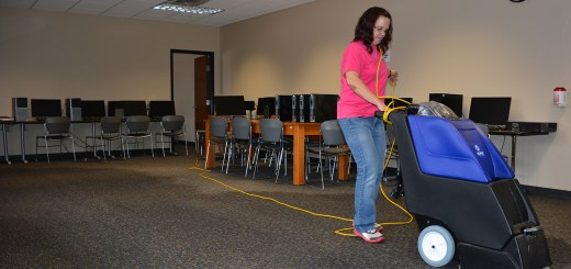 Kim Clark of Chadron, cleans flood water in Old Admin, Room 131, Tuesday, March 8. -- Photo by Evan L. Brooks
