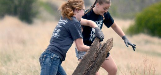 Bailey Broderick, left, 20, sophomore of Rapid City, South Dakota, and Teren Hanson, 22, senior of Casper, Wyoming, put an old railroad tie in a pile during The Big Event for Discover NW Nebraska Saturday. - Photo by Sara Tweet