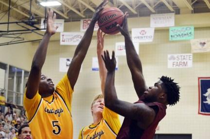 Alan Herndon (5), junior of Colorado Springs, Colorado, blocks a shot from CSC's Michael Johnson, freshman of Nassau, Bahamas.