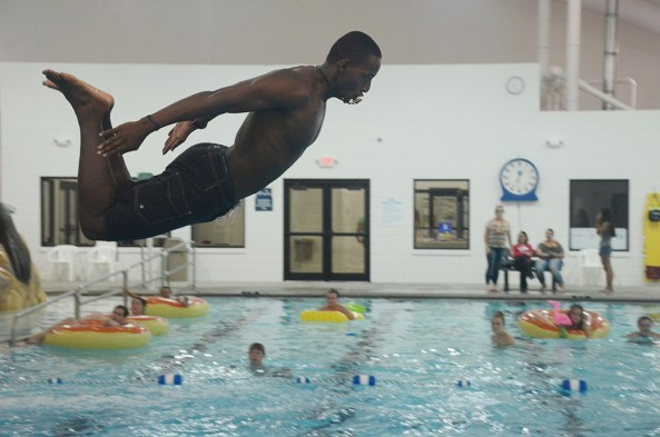 Sophomore Jeff Olly, 19, of Denver, Colorado, flies off the diving board, Friday, during the CAB pool party at the Chadron Area Aquatics and Wellness Center.