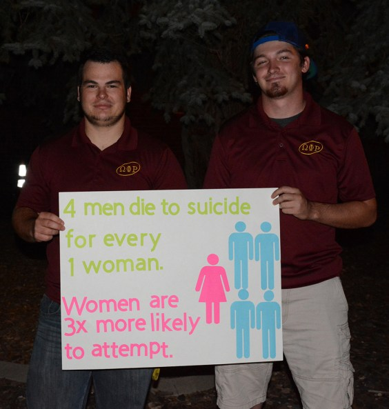 Members of Omega Phi Rho, Stormy Roy, left, 21, senior of Wright, Wyoming and Kodiak French, 21, senior of Wright, Wyoming, hold a sign that contains facts and information about suicide, Saturday at Suicide Prevention Walk.