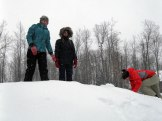 Emma A. and Kali pack down the mound while Liana adds more snow.