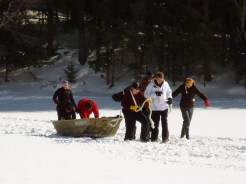 Annie, Grant, Jason, and Nick pull the sledge as Shane, Madi, and Erin B. push
