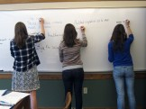 Students write sentences from their homework assignment on the board.