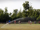 Students enjoy a cool game of Ultimate Frisbee and even cooler sprinklers.