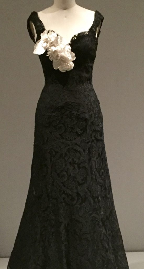Manus x Machina - Chanel evening dress, 1937-38, haute couture, hand-sewn, machine-made black silk-rayon lace, hand-shaped with wire and horsehair at sleeves, hand-attached, machine-sewing black rayon crepe liner, white linen floral corsage with die-cut, hand embossed and hand-assembled flowers.