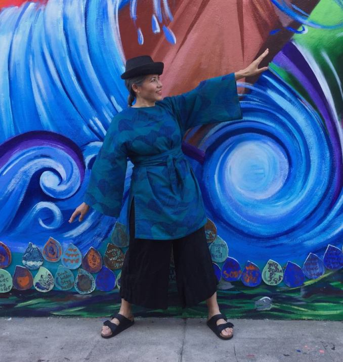 Asian woman wearing blue tunic and a black hat and black pants posing with arms out at an angle in front of a wall painted with blue waves.