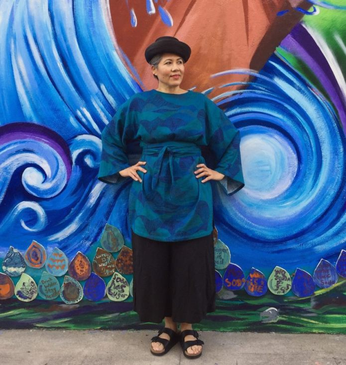 Asian woman standing in front of mural painted with waves of blue, wearing a blue tunic, black hat and black pants.
