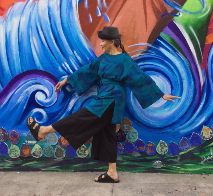 Asian woman wearing black hat, blue tunic, and black pants striding forward in front of colorful mural with blue waves of water.