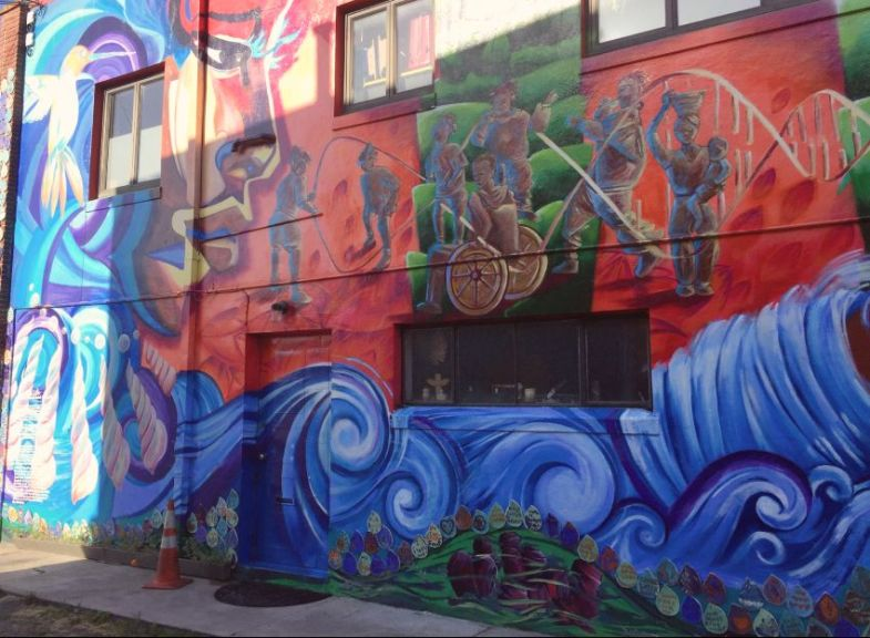 Mural with blue waves at bottom and people of color playing