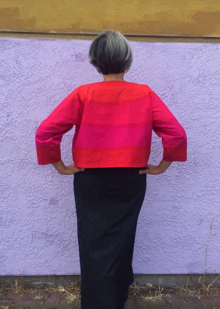 Woman standing with back to camera, hands on hips wearing bright orange, hot pink top