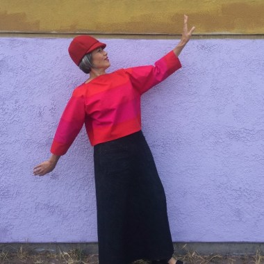 Asian woman wearing red hat, bright orange and hot pink top and denim maxi skirt standing in front of white wall with yellow strip at the top, posing with one arm up and the other down.