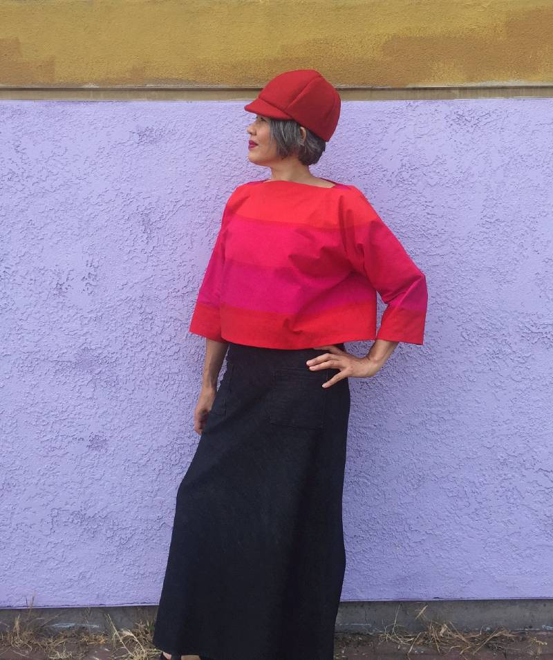 Asian woman in Suri top in bright orange and hot pink standing with hand on hip and wearing a denim skirt.