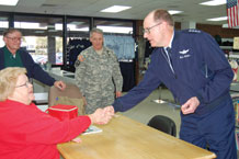 "(Photo by Thea Skinner) Gen. C. Robert Kehler, Air Force Space Command commander at Peterson Air Force Base shakes the hand of Sandra Trean, Airman's Attic volunteer before handing her a Guardians of the Higher Frontier coin at the ""Attic"" Feb. 23. Airman's Attic marked a one year anniversary in a new location in February. The Airman's Attic is co-located with the Family Service loan closet at building 1425, across the parking lot from the base chapel."