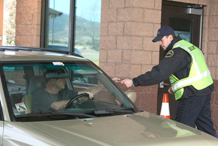 Gate guard Aaron Crow returns an identification card to a driver at Gate 1 March 23.