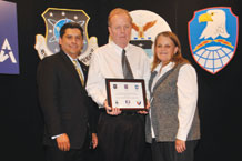 (U.S. Air Force photo/Robert Lingley) Jack Riley and his wife, Sandy, accept the Department of Defense/Pikes Peak Region Military Installation 2009 Small Business Contractor of the Year award from Greg Lopez, U.S. Small Business Administration's Colorado district director. Mr. Riley is the Schriever Air Force Base Satellite Dish Dining Facility owner/operator.