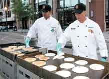 Sgt. Shobhan Desai, 43rd Sustainment Brigade, left, and Spc. Albert Fuentes, 549th Quartermaster Company, 43rd SB, flip pancakes at the Pikes Peak or Bust Rodeo Street Breakfast June 24.