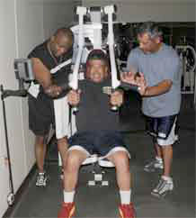 "Steven Dozier, left and Miguel Hernandez, right, help Luis Aurgos with fitness training equipment at Forrest Fitness Center Tuesday. This is the type of teamwork that will be on display during the upcoming ""Burn off the Wait"" program."