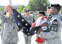 21st Security Forces Squadron Airmen lower the Colors during Retreat at the 21st Space Wing Headquarters building flagpole June 30. Col. Emily Buckman, 21st Mission Support Group commander led the Retreat formation which was comprised of 40 local Airmen. As directed by Col. Jay Raymond, 21st SW commander, each Peterson group or squadron will be responsible for conducting Retreat once a month on a rotating basis. (Air Force photo by Tech. Sgt. Ray Bowden)