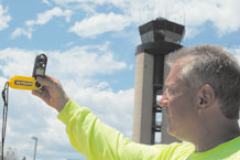 Joe White, Embassy Lawn and Landscaping Inc. pest controller, measures the wind speed near the Federal Aviation Administration control tower July 1. The landscaping company purchased three Speed Tech Skymate SM-8 Windmeters that measure wind speed, to prevent herbicides from drifting and possibly harming personnel and vegetation. Staff will not spray herbicides when the wind speed is more than 7 mph. (Air Force photo by Thea Skinner)