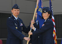 Lt. Col. Jean Eisenhut, 3rd Space Operations Squadron commander, accepts the guidon from Col. Stanford Kekauoha, 50th Operations Group commander, in a change-of-command ceremony in front of the DeKok Building June 23. Colonel Eisenhut succeeded Lt. Col. Brent McArthur as commander of 3rd SOPS.