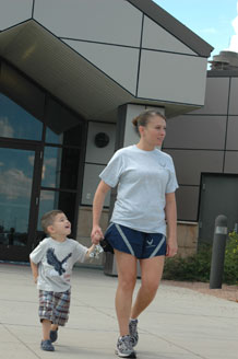 Staff Sgt. Crystal Martinez and her son Montana exit the Schriever Child Development Center July 27. Beginning August 17, the CDC will begin offering before and after-school care for families with kindergarten and elementary school-age children.