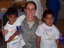 Airman 1st Class Sabrina Hibbens makes friends with a pair of Afghanistan youth. Airman Hibbens volunteered for a deployment in support of the U.S. special forces.