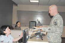 Airman 1st Class Chelsea Pennington, 21st Security Force Squadron, assists Army Capt. David Pyatt, at the Defense Biometric Identification System station located inside Bldg. 350. Members needing access to Peterson must register with DBIDS in order to remain eligible for base access. (Air Force photo by Thea Skinner)