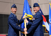 Lt. Gen. Larry James, 14th Air Force commander, presents the 50th Space Wing guidon to Col. Wayne Monteith in a change-of-command ceremony here Aug. 20. Colonel Monteith succeeded Brig. Gen. Cary Chun as commander of the wing.