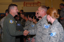Col. Wayne Monteith, 50th Space Wing commander, congratulates Schriever Airmen selected for promotion to staff sergeant during a party in the Main Fitness Center here Aug. 21. The Air Force made the selection list available Aug. 20. Fifty Schriever Airmen were selected for promotion to E-5.