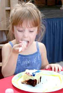 Family member Zoe Lee, 3, enjoys cake during the Rocky Mountain USO at Fort Carson's first anniversary celebration Sept. 16.