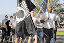A flight of Airmen, Soldiers and civilians jog the last leg of the 24-hour POW/MIA run Sept. 18 before posting the POW/MIA flag in front of the base chapel. The end of the run signified the beginning of Peterson's POW/MIA Recognition Day ceremony and marked the conclusion of National POW/MIA week. The 21st Space Wing hosted several events during this week including a Reveille ceremony, the run and a candlelight vigil. Col. (ret) Gordon Scott, a former POW, was the guest speaker Friday at the chapel. (Air Force photo by Larry Hulst)