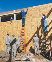 Cadets install walls for the sanctuary's new barn which will house horses, feed and equipment. (Photo by Ann Patton)