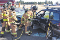 "21st Space Wing firefighters use a hydraulic rescue tool, also known as the ""jaws of life,"" to peel back the metal of a smashed car door so they could safely extract an injured driver. Firefighters and rescue workers were on the scene of a simulated drunk driving crash Nov. 10 on Peterson Air Force Base. The event, Every 15 Minutes, was hosted by U.S. Northern Command and included participation from the 21st Space Wing's firefighters, security forces and emergency medical teams. The anti-drug event is meant to leave a visual image that will deter Airmen from drinking and driving, event organizers said. (Air Force photo by Dennis Howk)"