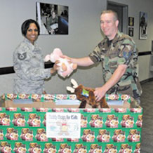 Tech. Sgt. Tanisha Hunter, 21st Space Wing command section, gives Tech. Sgt. Thom Moore, 21st SW ground safety technician, a stuffed animal for a holiday Teddy Bears for Kids drive. The collected Teddy bears will be delivered Dec. 22 to children in the pediatric ward of Penrose St. Francis Medical Center. The drive continues through Dec. 11. Teddy bears can be dropped off in the Safety office, Building 845, room 107, or at Child Care Connections, 125 N. Parkside, Suite 202, Colorado Springs. (Air Force photo by Monica Mendoza)