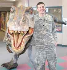 """Spc. Kelby Hershey, Company D, Division Special Troops Battalion, 4th Infantry Division, hangs out with his brother, Stephen Hershey, """"Baby T. Rex,"""" at Mountain Side Elementary School Dec. 16. Stephen was at the school to promote the upcoming """"Walking with Dinosaurs"""" show at the World Arena Jan. 21-24."""