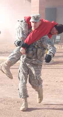 "Photos by Zvia Bird.  Staff Sgt. James Seybert fireman carries an ""injured"" Soldier during evacuation training after a mock fire breaks out at a local hospital."