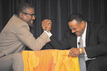 "Malcolm X, portrayed by Ersky Freeman (left) and Dr. Martin Luther King Jr., portrayed by Shelby Wallace, settle their opposing views with an arm wrestle during a powerful drama, ""The Meeting."" The performance was Jan. 13 at The Club as part of the 21st Space Wing's Dr. Martin Luther King Jr. remembrance event, focusing on heritage and cultural diversity. (Air Force photo by Craig Denton)"