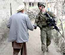 Pfc. Robert J. Goggins, gunner, Company D, 2nd Battalion, 12th Infantry Regiment, 4th Brigade Combat Team, 4th Infantry Division, shakes hands with a local from the Kandagal village in the Manogai District of eastern Afghanistan's Kunar province.