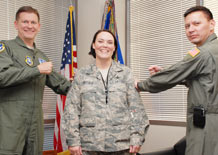 """Master Sgt. Amber Mitchell(center), 1st Space Operations Squadron, prepares for her new stripes to be """"tacked on"""" from Col. Wayne Monteith(left), 50th Space Wing commander, and Col. Stan Kekauoha, 50th Operations Group commander, in Colonel Monteith's office March 4. Sergeant Mitchell is one of 1,269 master sergeants selected for promotion this year.  (U.S. Air Force photos by Tech. Sgt. Stacy Foster)"""