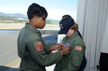 Cadet 1st Class Solange Eddy, Cadet Squadron 06, affixes Scott Kleinschmidt's nametape to his flight suit during his visit to the Air Force Academy April 8 through Saturday. Photo by Johnny Wilson