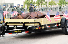 Airmen salute a beam from one of the collapsed towers of the World Trade Center as it arrives on base April 26. The beam, which the Port Authority of New York and New Jersey donated to Schriever, will become part of a future memorial on base to commemorate the events of Sept. 11, 2001. (U.S. Air Force photo/David Ahlschwede)