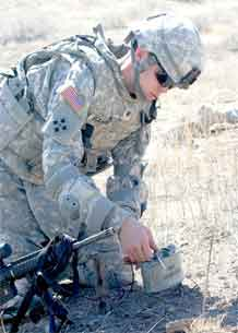 Spc. Dustin Eckard, a combat engineer with Company C, 2nd Special Troops Battalion, 2nd Brigade Combat Team, 4th Infantry Division, arms a claymore mine during a demolition training at Range 121A.