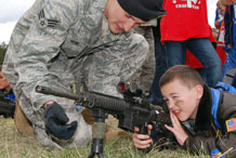 Senior Airman Jacob Heine familiarizes Andy Miller with an M-4 rifle during Operation Junior Deployer at the Air Force Academy May 1, 2010. Airman Heine is a patroller with the Academy's 10th Security Forces Squadron.