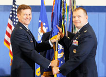 Col. Michael Finn, the new 50th Network Operations Group commander, receives the guide-on from Col. Wayne Monteith, 50th Space Wing commander, during a change-of-command ceremony at the fitness center May 14. (U.S. Air Force photo/Dennis Rogers)