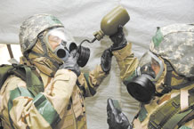 PETERSON AIR FORCE BASE, Colo. -- Col. Kimerlee Conner, 21st Mission Support Group commander (right), assists Chief Master Sgt. Michael Hayter, 21st MSG first sergeant, as he drinks water from a canteen using his gas mask drinking apparatus on May 7. This is one of many tasks evaluated during the quarterly exercise Condor Crest. This exercise was designed to test the wing's ability to perform deployment and field operations and how to survive in a chemical environment. (U.S. Air Force photo/Craig Denton)